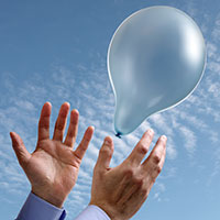 Person's hands releasing a balloon into the sky